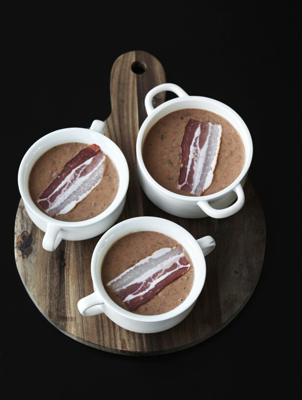 5. Hell blandingen i smurte ramekiner (eller i 8–10 små, ildfaste keramikkformer). Skjær bacon i mindre biter, og fordel dem oppå hver porsjon leverpostei. Varm opp ovnen til 180°. Sett de fylte formene i en dyp stekeovnsplate. FOTO: Betina Hastoft