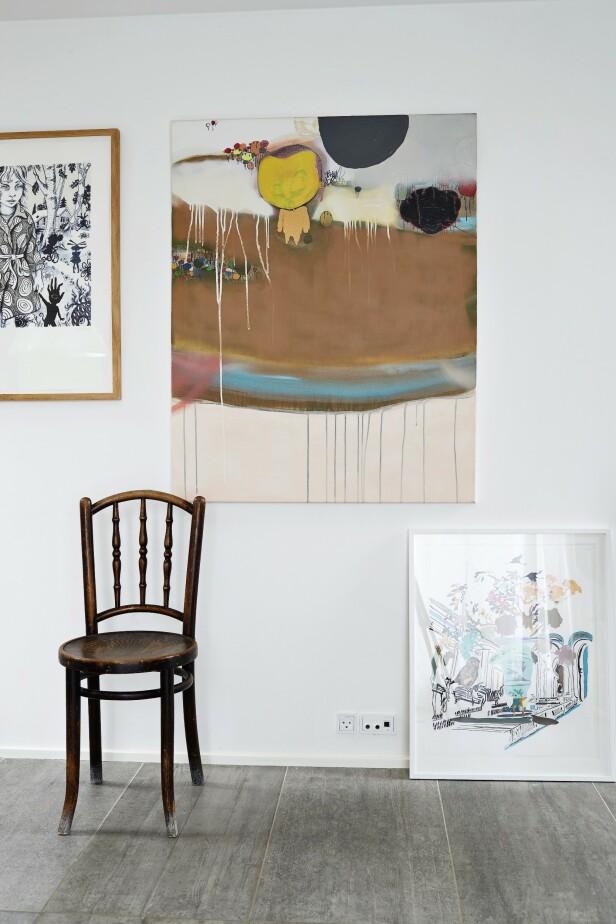 Moderne kunst og gamle møbler gir en fin kontrast, som her, der en stol fra et loppemarked står ved det store maleriet av Kristoffer Akselbo. Ved siden av henger et kunstverk av Julie Nord, og på gulvet står et verk av Ann Sophie Stærk. FOTO: Ida Schmidt