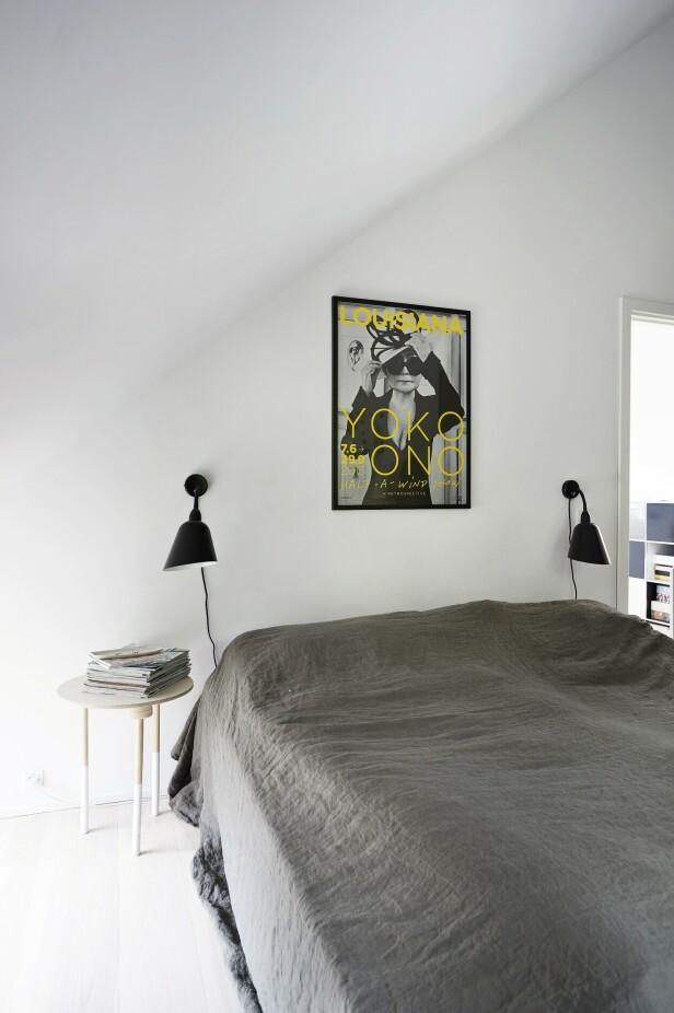 Også på soverommet har en kunstplakat sneket seg inn. Den er fra det kjente museet Louisiana. Sengelampene er designet av Arne Jacobsen og er fra &tradition, og nattbordet har parets datter Olivia laget på sløyden. Sengeteppet er fra Merci Merci i Paris. FOTO: Ida Schmidt