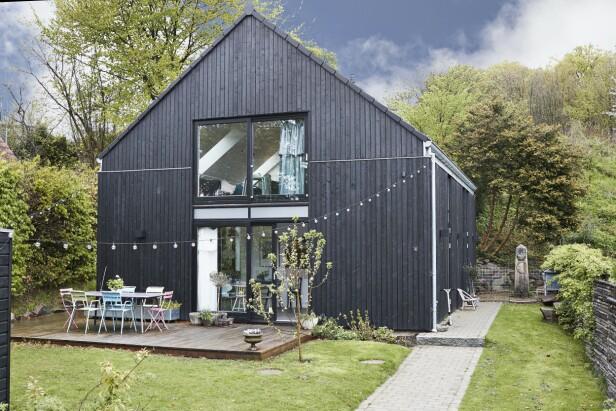 Det svartmalte trehuset er tegnet av arkitekten Bjarne Frost, og minner familien om gamle danske sommerhus. Hustypen heter «One Room», og er inspirert av arkitekturen til en låve. FOTO: Ida Schmidt