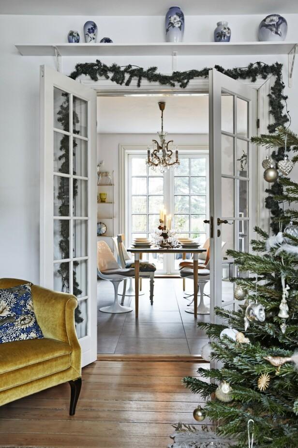 De franske dørene mellom stuen og spisestuen har Nina pyntet med grankvister for å ramme inn og skape en lun følelse. Den gule stolen er kjøpt brukt, og puten er fra Eline Engen. FOTO: Dianna Nilsson