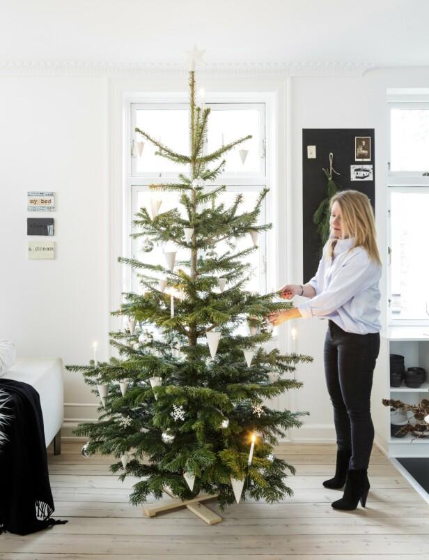 Juletreet er enkelt pyntet med hvite porselensornamenter som Ditte selv har laget. I tillegg har de sølvfargede kulene og den hvite stjernen i toppen alltid fast plass på treet. Tips! La selve treet være i fokus ved å holde pynten enkel og koordinert. FOTO: Anitta Behrendt