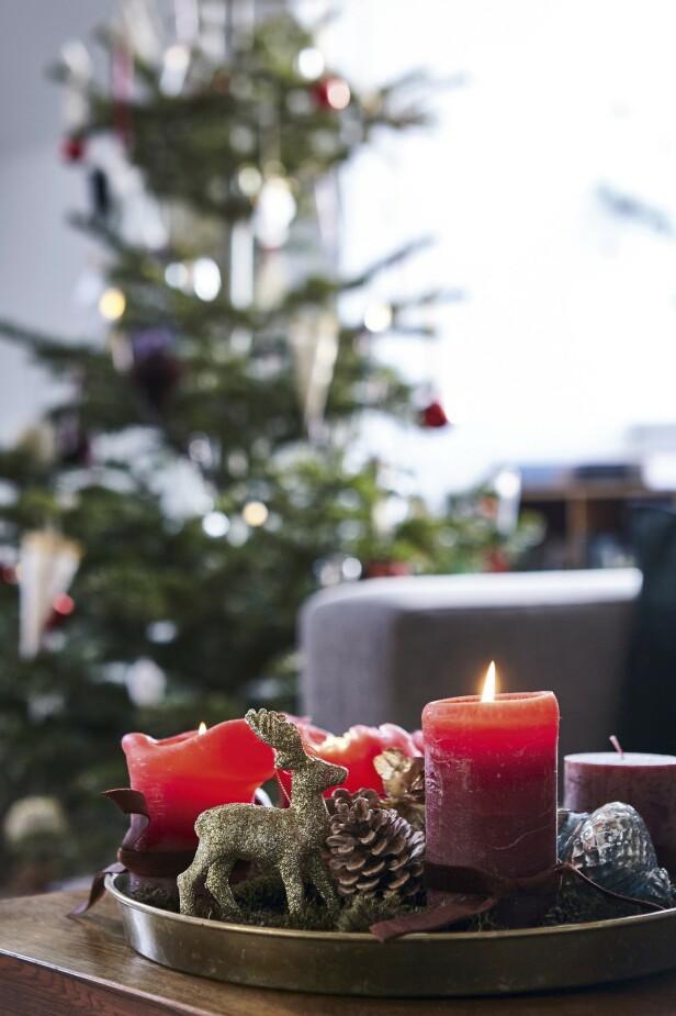 Kongler, reinsdyr og julekuler pynter opp rundt adventslysene. Tips! Lag din egen adventsstake på et fat med fire kubbelys og sjarmerende pynt. FOTO: Lene Samsø