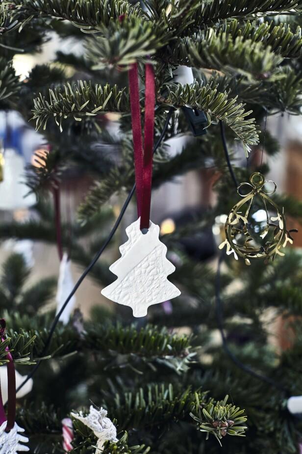 Julepynten i fimoleire har Sarah laget selv. Hun har brukt et gammelt blondestoff for å gi overflaten en delikat struktur. For å tilføre farge, har hun valgt røde silkebånd. FOTO: Lene Samsø