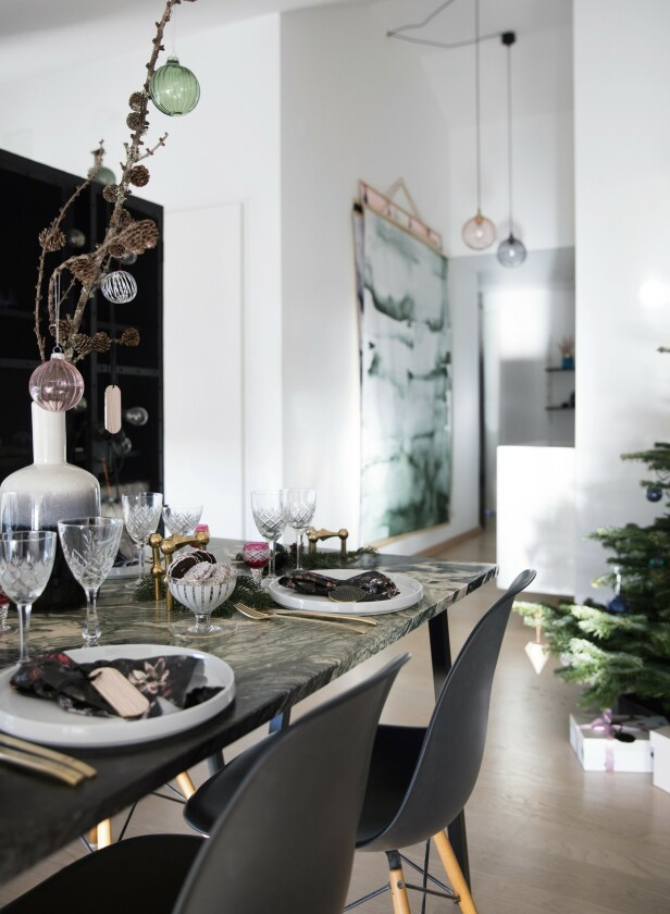 Nynne blander gjerne gamle krystallglass med morderne tallerkener i grafisk utforming, messingbestikk og messingstaker som gjør bordet oppdatert og ikke for pent. Bordet er en gammel plate i marmor på bordbein fra Hay. Stolene er klassiske Eames. FOTO: Kira Brandt