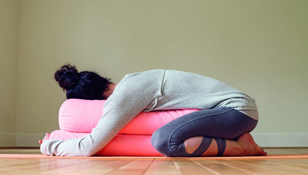 BARNET MED FULL STØTTE (Salamba Balasana): Denne foroverbøyen strekker ryggen, letter anspente skuldre og bidrar til å roe ned sinnet. Fordi den etterlikner babyenes hvilestilling, kan den også gi en ekstra følelse av trygghet og støtte.Denne øvelsen virker bra mot menstruasjonssmerter. Den lindrer ekstra godt hvis du plasserer nevene foran eggstokkene som vist på bildet. Len deg forover med hendene her, og gjør for øvrig som beskrevet over.