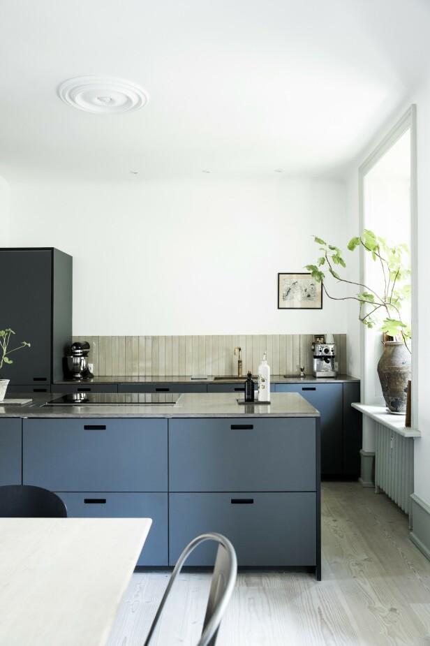 De har lagt kjøkkenet til leilighetens største rom, og det er derfor god plass til et hyggelig kaffehjørne her. Paret har valgt et kjøkken i fargen Pewter fra danske &Shufl, som lager fronter til Ikea-kjøkken. Veggflisene er fra File Under Pop. FOTO: Tia Borgsmidt