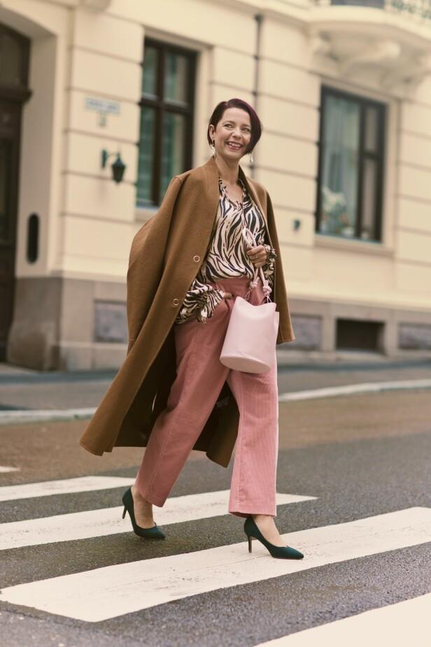 Kåpe (kr 1200), bukse (kr 400) og øredobber (kr 70, alt fra Kappahl), bluse (kr 1000, Part Two), veske (kr 400, Don Donna) og pumps (kr 200, H&M). Tips! Sett farge på antrekket ved å bytte ut jeansen med en rosa bukse i kordfløyel. FOTO: Astrid Waller