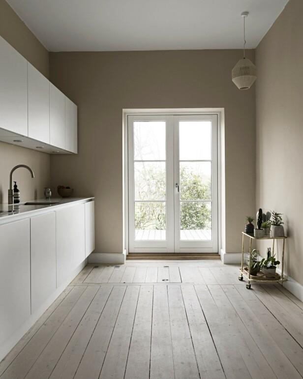 Fra kjøkkenet er det utgang til hagen og utsikt over Helsingør og Øresund. Kjøkkenet er holdt helt enkelt med hvite flater. Det er ikke mye nips her, men de som får stå framme, er nøye utvalgt. FOTO: Peter Kragballe