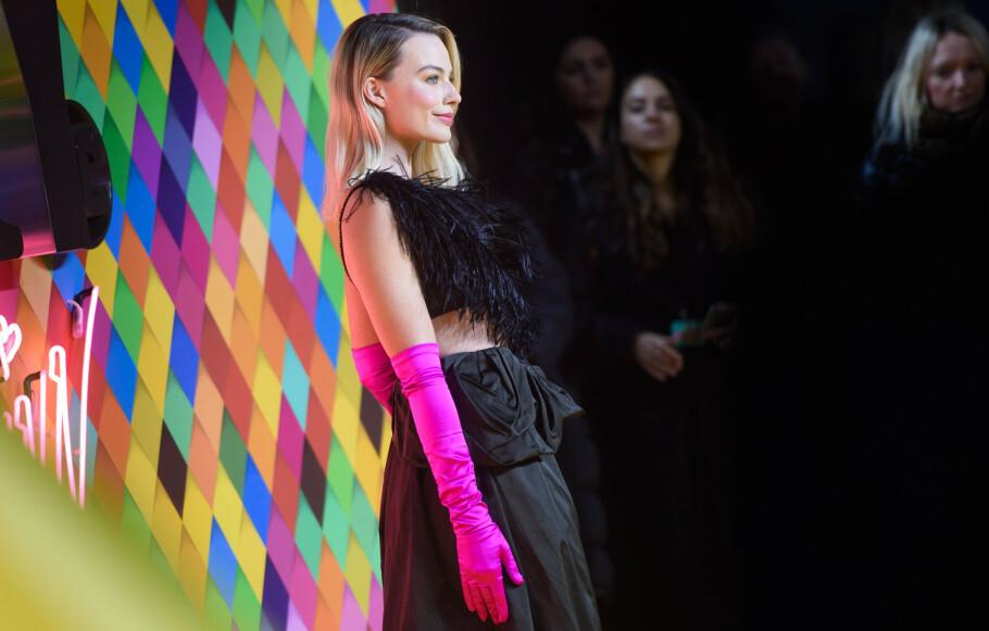 TRENDY: Margot Robbie er ofte tidlig ute med å teste nye trender, her med et par sjokkrosa hansker. Foto: NTB Scanpix
