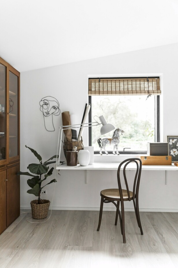 Kunstverket på veggen er laget av svartmalt kobbertråd som er sirlig bøyd så den ligner et hode. Og dens skjeve linjer bryter med de ellers rette linjene i rommet. FOTO: Julie Wittrup og Mikkel Dahlstrøm/Another Studio