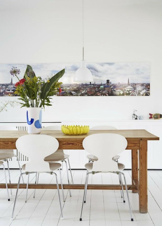 Vasen på spisebordet er fra Can Family, og bananfatet er fra Dora. Tips! Hvis du har et åpent kjøkkenallrom, kan du markere spiseavdelingen med et langt bilde. FOTO: Anitta Behrendt