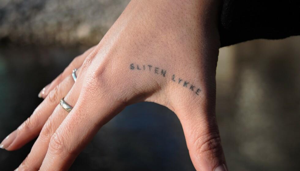 TATOVERING: - Det betyr at uansett hvor mørkt det er og hvor sliten du er, så finnes det alltid lykke. På det mørkeste er det alltid noen der som gir deg lykke, forteller Thea om tatoveringen på hånda. FOTO: Kamilla Skjørland