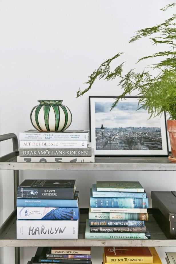 Hvis du samler bøkene dine i dekorative stabler på en rullevogn i stedet for en hylle, kan du lett flytte rundt på dem. Vognen i industriell stil er fra Fil de Fer, vasen er vintage og fra Kähler. Fotokunsten er laget av Robin Skjoldborg. FOTO: Birgitta Wolfgang Bjørnvad