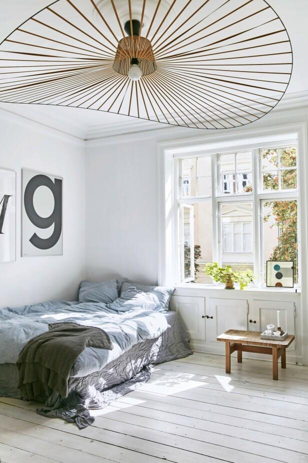 Taklampen «Vertigo» fra Petite Friture skiller seg definitivt ut fra mengden. Benken under vinduet er fra Børge Mogensen. Sengetøy og pledd er fra Aiayu, mens plakatene er fra Playtype. Tips! Hvis du henger en stor, skulpturell lampe i taket, trenger du ikke så mye annet for å gi rommet massevis av personlighet. FOTO: Birgitta Wolfgang Bjørnvad