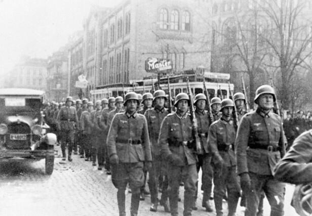 TYSKE TROPPER: Leif fikk streng beskjed av foreldrene om at man ikke står og beundrer fienden som kommer masjerende. Dette bildet er tatt etter den tyske invasjonen av Norge 9. april 1940.  Den tyske troppen marsjerer gjennom Karl Johans gate, med Stortinget i bakgrunnen. FOTO: NTB scanpix
