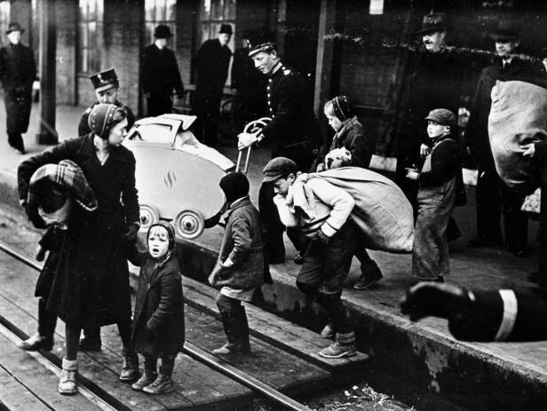 HJELPERE: Dette bildet er tatt i Sverige 21. april 1940. Norske flyktninger på gjennomreise i Karlstad i Sverige. Kvinnen med barn får hjelp av togpersonale på jernbanestasjonen. Selv ble Leif, moren og lillesøsteren tatt med til Charlottenberg togstasjon for ferden videre til Kjesäter mottakssentral for flykninger. FOTO: NTB scanpix