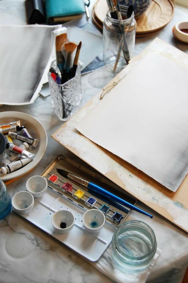 Katarina sitter ved kjøkkenbordet når hun maler. Hele leiligheten vasker hun på en time. FOTO: Katarina Danielsson