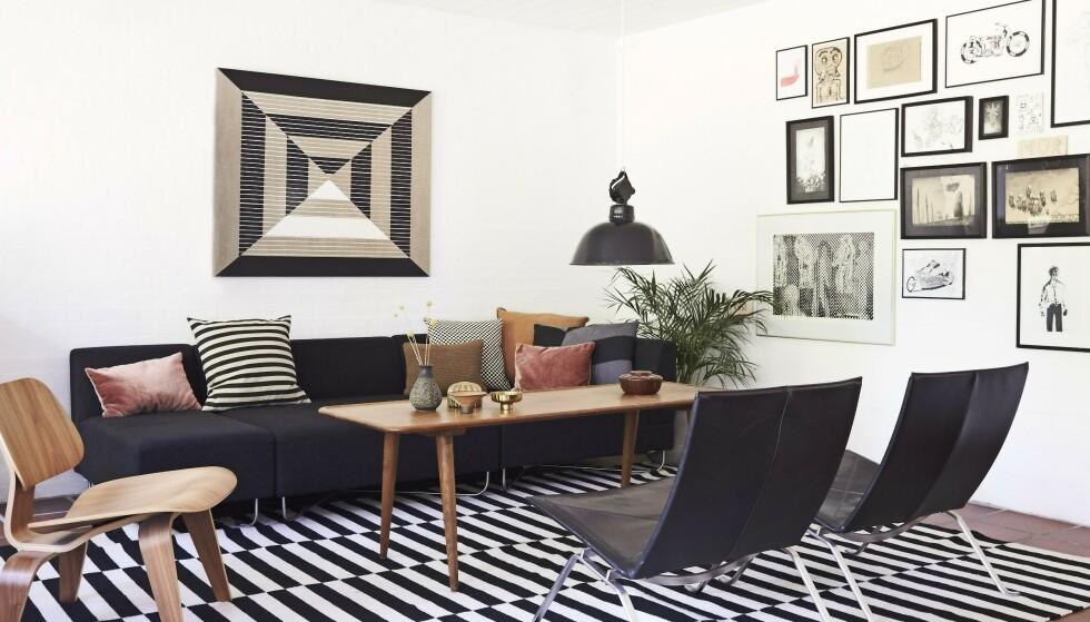 Sofaen fra Bolia.com er fylt med puter fra bl.a. H&M Home, Vintage 415 og Ikea. Wegner-bordet og lampen er vintage, Poul Kjærholmstolene er fra Fritz Hansen, og teppet er fra Ikea. Eames-stolen i valnøttre er fra New York. Over sofaen henger et kunstverk av Anne Aarsland. Tips! Hvis du innreder stramt og grafisk, kan du la veggene fylles med kunstverk. FOTO: Ditte Capion