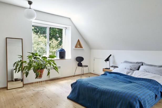 Et blått sengeteppe i ull fra Snorres besteforeldre gir farge til det romslige soverommet. Sengetøy, speil og taklampe er fra Ikea. Mauren-stolen og nattbordet er kjøpt brukt, og bordlampen er fra Louis Poulsen. Kunstverket i vinduskarmen er kjøpt på flidmarked. FOTO: Ditte Capion