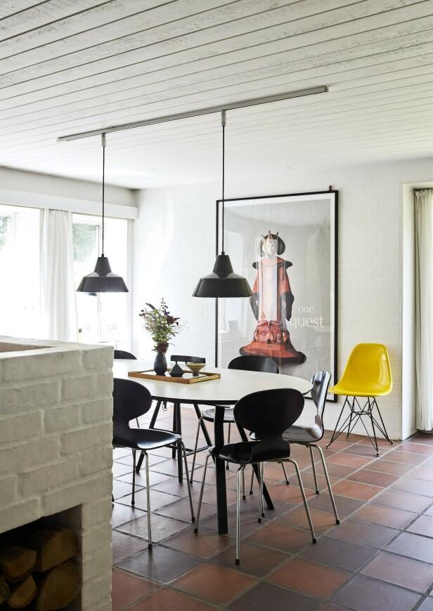 Den store plakaten på veggen er en filmplakat fra «Star Wars». En gul Eames-stol lyser opp, mens resten av møblene er svarte og hvite. Lampene fulgte med huset. Tips! La en kjempestor plakat styre stilen i et rom, slik det er gjort her i spisestuen. FOTO: Ditte Capion