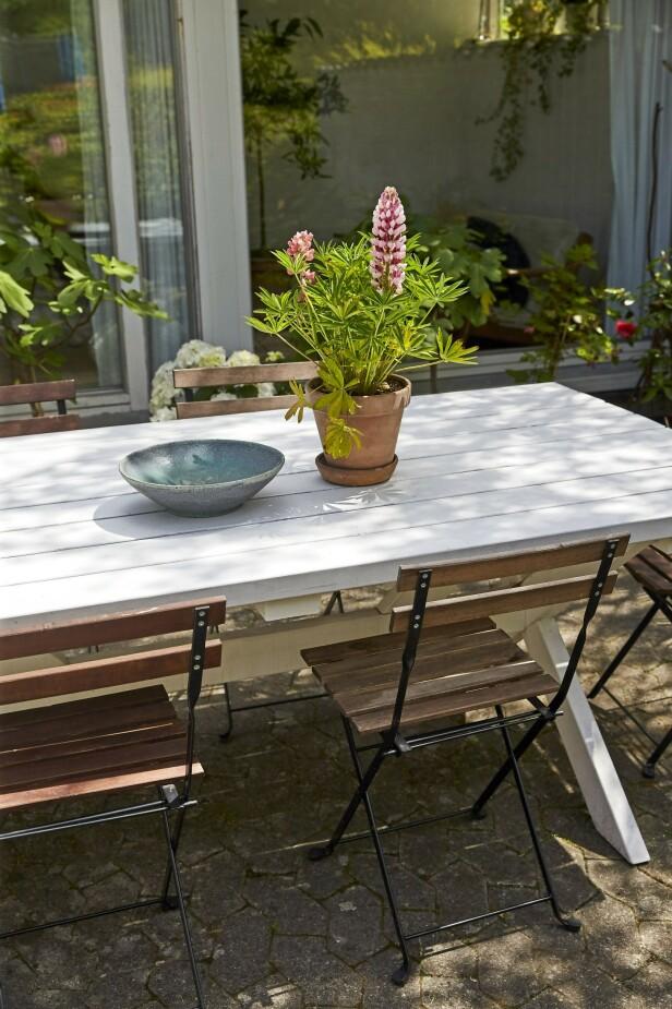 Terrassen ligger rett utenfor utestuen, og her har paret laget en liten kosekrok. Spisebordet er bygd av en snekker, stolene er fra Ikea, og det turkise keramikkfatet har Janni selv laget. FOTO: Ditte Capion