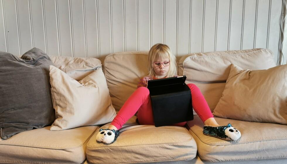 <strong>SOFASKOLE:</strong> Dorotea er ganske avslappet der hun har funnet sin plass i sofaen, med nettbrettet på fanget. FOTO: Privat
