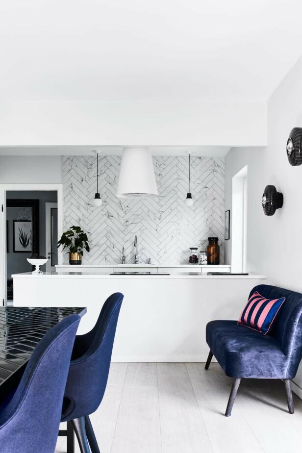 Har du plass, er det koselig å ha en liten sofa på kjøkkenet. For da kan den som lager mat, få selskap. Sofa Cozy Living, pute fra Bungalow og urtepotte fra Ilva. Kakeoppsats fra Royal Copenhagen, fliser fra Mosaikhjørnet og lamper fra &tradition. Kjøkkenvifte fra Trepol og kjøkken fra Invita. Tips! Hvis du ikke har overskap på kjøkkenet, kan du skape en flott effekt ved å flislegge veggen over kjøkkenbenken helt opp til taket. FOTO: Høeg + Møller