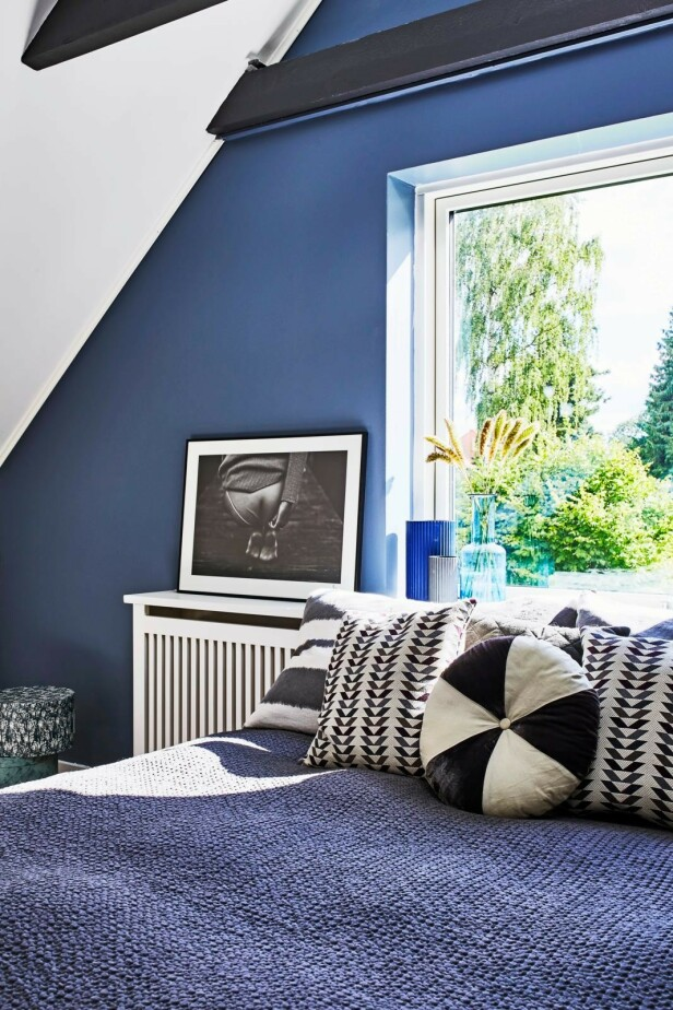 Har du et møbel i en markant farge, kan du sette det sammen med mindre ting i samme farge, det gir et roligere uttrykk. Her en blå glassvase fra Louise Roe i stuen med den blå sofaen. Tips! Miks puter med forskjellige mønstre, men i samme farger. Det virker livlig og harmonisk på samme tid. FOTO: Høeg + Møller
