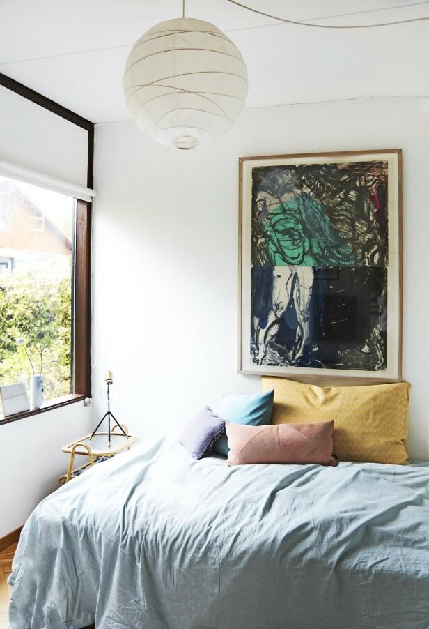 Bildet på veggen over sengen er laget av Per Kirkeby. Tips! Innred sove- rommet enkelt, men la fargene spille på et bilde, på sengeteppet og putene. FOTO: Nicoline Olsen