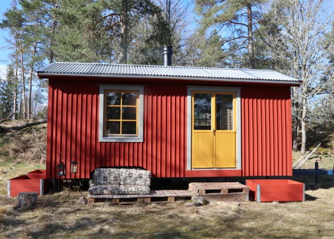 EN LITEN RØDMALT STUGA: Det lille huset i skogen er bygget av 70 prosent gjenbruksmaterialer og innredet med mange loppemarkedfunn. FOTO: Privat