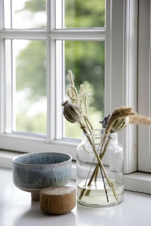 Naturlige materialer gjør Louise glad, og hun bruker dem både hjemme og i firmaet sitt. Små, fine oppstillinger pynter opp i vinduskarmene. Her er en keramikkskål med vakker, blå glasur fra Studio Arhøj, en håndlaget treskje og et glass med funn fra hagen. FOTO: Stine Christiansen