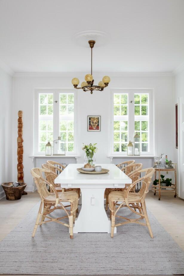 Louise har selv malt det gamle langbordet i spisestuen hvitt. Totempælen har hun funnet på en reise til Bali. Lysekronen er antikk. Tips! Hvis du har flettestoler i naturmaterialer, vil et hvitt bord framheve stolenes varme nyanser. FOTO: Stine Christiansen