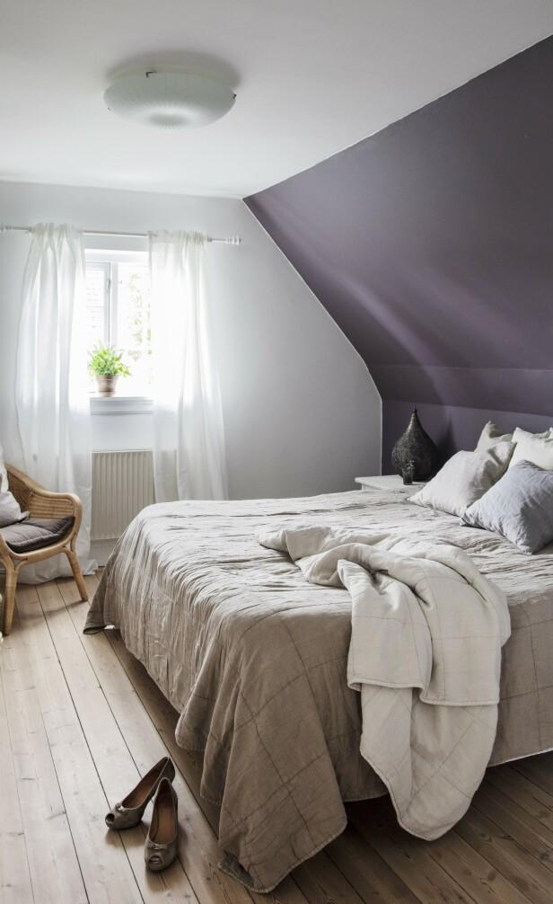 På det enkelt innredete soverommet i andre etasje har paret valgt å male en vegg i en mørk lilla nyanse. Tips! Ved å male en vegg på soverommet i en mørk nyanse skaper du en lun og koselig hulestemning. FOTO: Stine Christiansen