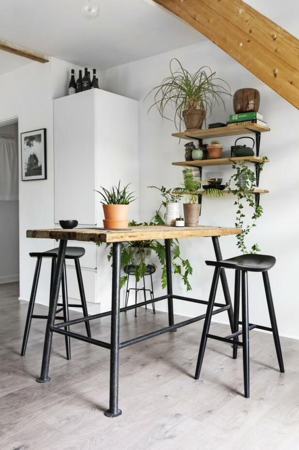 I et hjørne av kjøkkenet under trappen til annen etasje tar Fie og Jonas ofte morgenkaffen. Det høye plankebordet og barstolene skaper et uhøytidelig uttrykk. Tips! Svart, hvitt, metall og røft treverk. Sammen med grønne planter skaper det en rustikk og samtidig moderne stil. FOTO: Mettemaje Skøtt og Camilla Skøtt