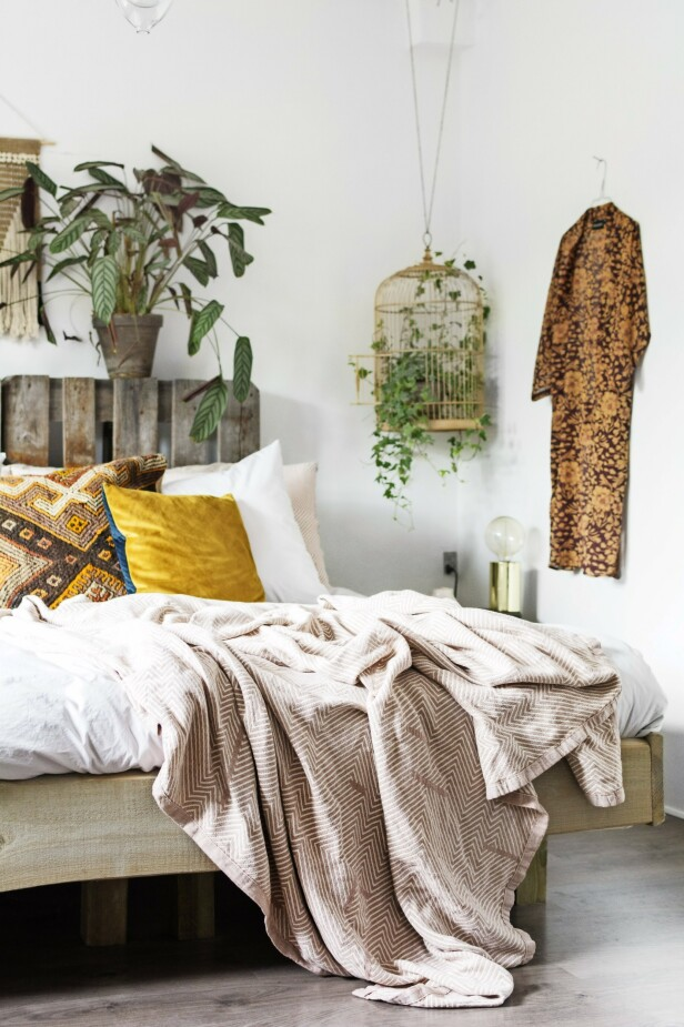 På soveværelset har sengen fått en sengegavl som er laget av en gammel pall. I hjørnet henger en litt annerledes potteskjuler – et fint, antikt fuglebur. Tips! Sørger du for nøytrale, lyse farger på de store flatene, er det fritt fram for å leke seg med farger og mønstre i interiøret. FOTO: Mettemaje Skøtt og Camilla Skøtt