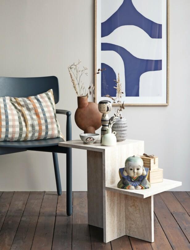 Stol (Skagerak), pute (Aiayu), bord (Ferm Living), plakat med blått mønster (The Poster Club), rustfarget vase (101 Copenhagen), gul vase (Stilleben), vase med riller (Notre Dame), kokeshi-dukke, liten skål, munk og trebokser (alt fra Ohayó). FOTO: Pernille Enoch
