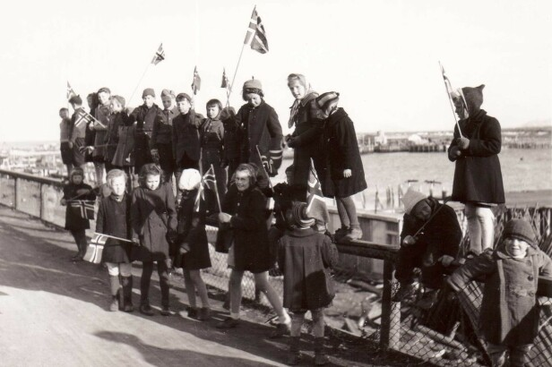 <strong>BARNLIG GLEDE:</strong> 17. mai-tog i Vadsø 1945 med barn som sitter på gjerdet. Vadsø havn i bakgrunnen. FOTO: Gunnar Fougner / Vadsø Museum / Ruija Kvenmuseum
