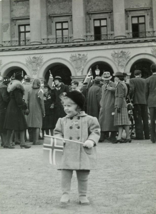 <strong>LITEN PIKE, STOR DAG:</strong> Lille Anne Margrete Holst fotografert foran slottet 17. mai 1945, i påvente av at kronprinsen skulle komme ut og vinke til folket. FOTO: Kjell Johan Saugstad / Oslo Museum