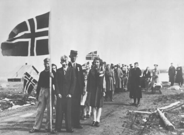 <strong>FEIRING:</strong> På gården Fjell, tilhørende Emma og Ole Mortensen, drev lærer Trygve Laudal skolen i Sagstua i Sør-Varanger. Her har han og elevene, samt foreldre, samlet seg for 17. mai-tog i 1945. FOTO: Finnmark Fylkesbibliotek / Digitalmuseet