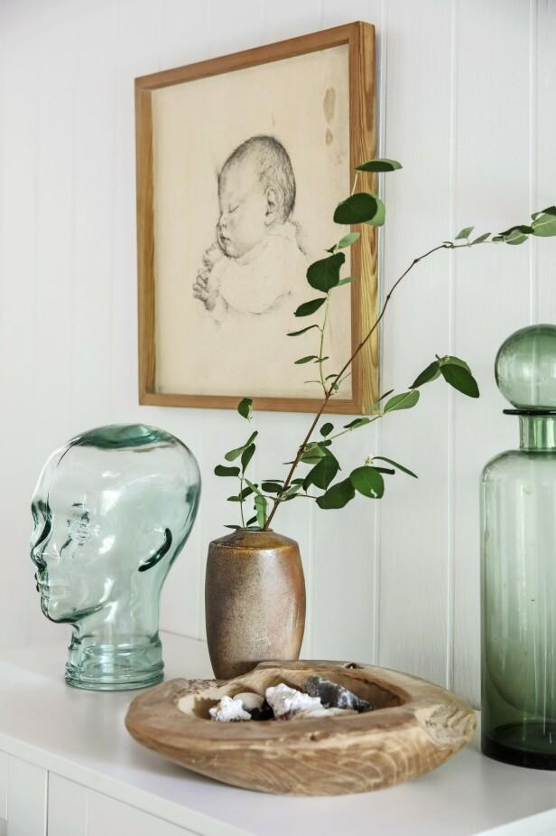 Sett grønt glass sammen med ting i tre og keramikk for å lette uttrykket. Tegning, glasshode og treskål er loppfunn. Den brune vasen er av keramikeren Sten Børsting, mens karaffelen er fra House Doctor. FOTO: Christina Kayser O.