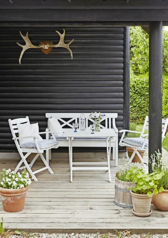 Hvite hagemøbler trenger slett ikke å være kjedelige. Tilsett friske blomster og lyse tekstiler som gir øyet ro og samtidig understreker sommeridyllen.