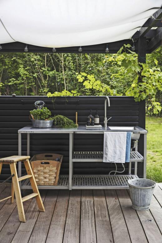 Et utekjøkken er både praktisk og dekorativt. Du kan satse på et møbel med integrert vask som her, men et høyt plantebord kan også fungere til det meste. Utekjøkkenet er fra Outstanding, og kjøkkenhåndkleet er   fra Semibasic.