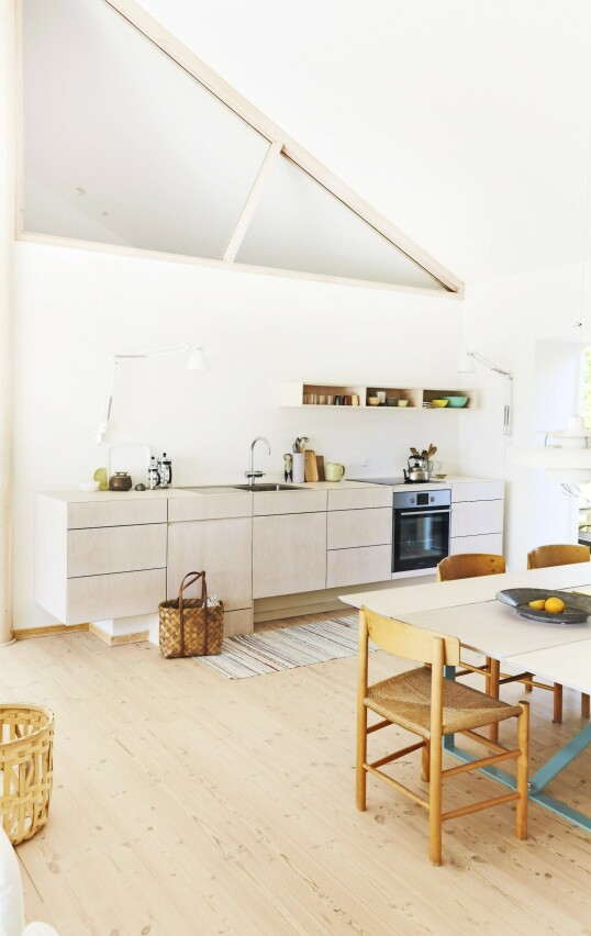 Claus Bjarrum har selv tegnet kjøkkenet, som er bygget i kryssfiner. Kryssfinerplater er både et lett og elastisk materiale framstilt av flere lag finer limt sammen på tvers. Tips! I et sommerhus trenger du ikke ha kjøkkenet fullt av serviser og andre ting og tang. Dropp overskapene, og skap enda mer følelse av rom. FOTO: Nicoline Olsen