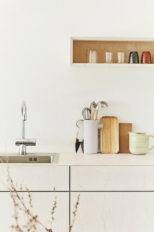 Holder du kjøkkeninnredningen og veggene i samme lyse tone, vil kjøkkenet virke større og mer luftig. Det hvitoljede kjøkkenet i kryssfiner har Claus Bjarrum designet selv. Tips! La enkle skjærefjøler av ulike treslag stå framme på benken. De gir den nødvendige lille varmen og kontrast til alt det hvite. FOTO: Nicoline Olsen