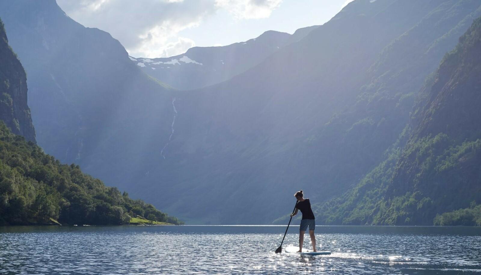 I VANNFLATEN: SUP eller ståpadling er blitt en populær aktivitet i norske fjorder, som her i Nærøyfjord. FOTO: Visitnorway.no