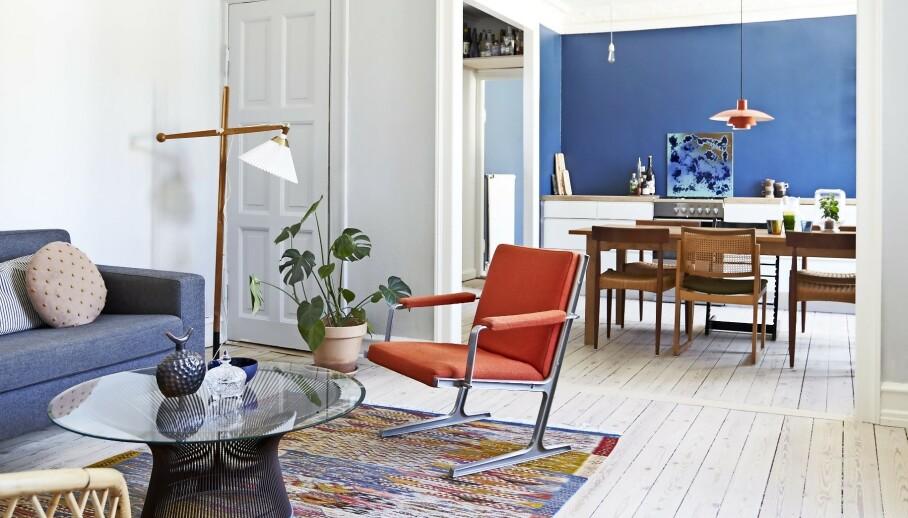 Blå og oransje nyanser går igjen i rommene og får dem til å henge sammen. På bordet står en blå skål fra Royal Copenhagen, en arvet krystallskål og en svart krukke med lokk fra Etiopia. Gulvteppet har Ann-Sofie og Casper kjøpt i Marokko. Den hvite pendellampen er designet av George Nelson. Tips! Velg et mønstrete gulvteppe i yndlingsfargene dine, og la fargene gå igjen på enkelte møbler, nips og vegger. FOTO: Lasse Wind/Claudi + Capion