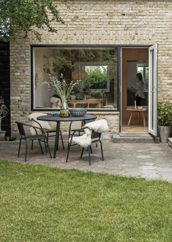 Sørger du for at det alltid er blomster i vasene på terrassebordet, kan utebordet fungere som en ekstra stue som får huset til å virke større. Det lille huset i gule teglstein er fra 1946. FOTO: Peter Kragballe