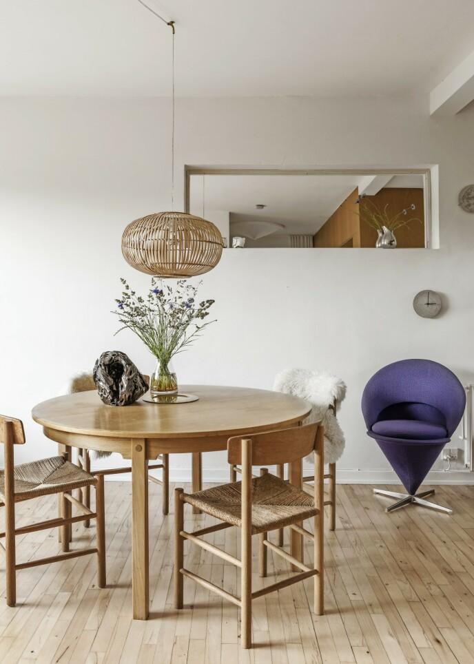 1947 designet Børge Mogensen den klassiske J39-spisebordsstolen. Den fås i ulike varianter av eik og med flettet sete av papirgarn. Den runde bambuspendelen over spisebordet henger i mindre format også i overgangen mellom stue og kjøkken. Gjentakelser skaper ro og sammenheng. FOTO: Peter Kragballe