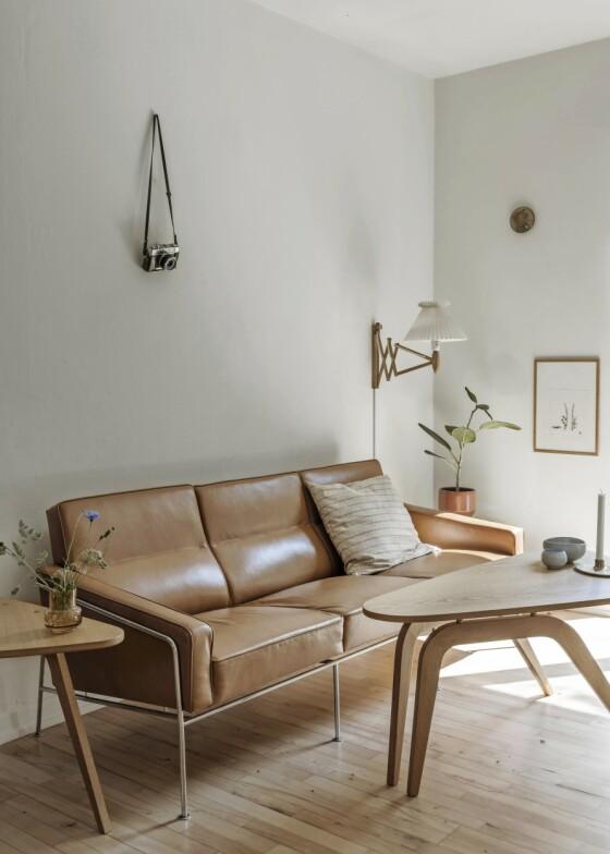 Arne Jacobsen designet opprinnelig Serie 3300-sofaen til blant annet SAS Royal Hotel i København. Det var samtidig som han designet de to ikoniske stolene Egget og Svanen. Tips! For at ikke stilrenheten skal gjøre hjemmet sterilt, er det viktig å bryte litt. Her har Line hengt et gammelt kamera på veggen for å skape kontrast og hjemmehygge. FOTO: Peter Kragballe